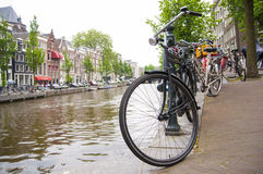 Detail of bicycle chained by canal in Amsterdam Stock Photos