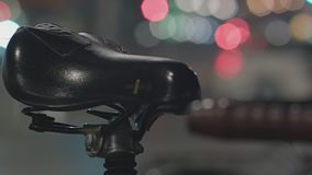 Detail Of Bicycle Saddle At Night. Detail Of Bicycle Saddle With Defocused Traffic In Background At Night. Urban Landscape stock video footage
