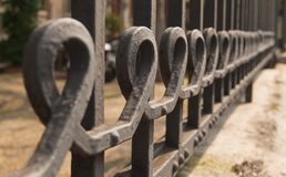 Detail of a big metal gate. Metal curls with sequency of geometric curves Stock Image