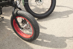 Detail of a bike with huge big wheels, on a sunny day Stock Images