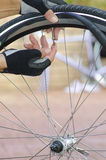 Detail bike repair with valve and tube. Detailed image of a bicycle repair, with two hands in biker gloves, with valve, tube, alloys and a bike in the blurred royalty free stock photo