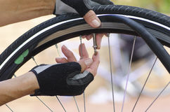 Detail bike repair with valve and tube II. Close up image of a bicycle repair, with two hands in biker gloves, with valve, tube, alloys and a bike in the blurred royalty free stock image
