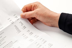 Detail of a bill. Elderly female hand holding a financial statement or a detailed business bill. Closeup image Royalty Free Stock Photo