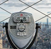 Detail of a binocular tourist telescope. And wire mesh grill overlooking the rooftops of New York City in a sightseeing, travel and tourism concept Stock Photography