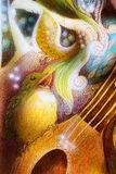 Detail of a bird singing a song of colorful ornaments on mandoline guitar Stock Photo