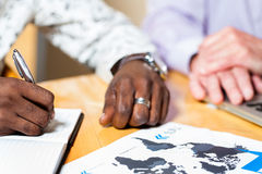 Detail of black business man signing documents. stock image