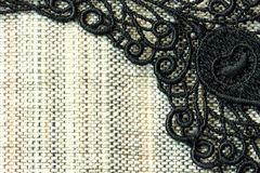 Detail of black lace on rough simple fabric Stock Photography