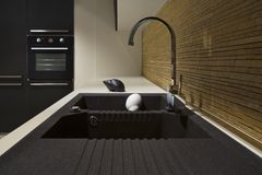 Detail of a black modern kitchen and wood. Detail of modern kitchen black and wood kitchen with sink, stove stock photo