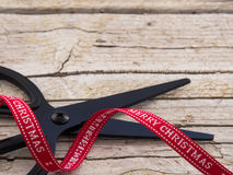 Detail of black scissor and red ribbon on wooden background. Detail of black scissor and christmas red ribbon on wooden background Royalty Free Stock Images