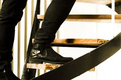 Detail of black suede boot and black jeans wearing man climbing interior staircase. Burglary concept. royalty free stock photos