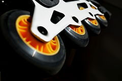 Detail of a black and yellow roller skates (in-line skates) in the darkness as a symbol of movement and speed Stock Photography