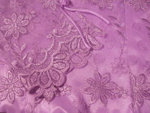 Detail of Blouse. Detail of a lavender Oriental blouse sleeve with floral lace overlay with shiny threads woven through it Stock Image