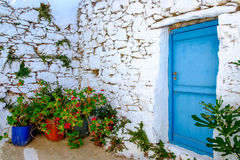 Detail of blue door, white stone wall and colorful flowers Stock Images