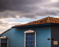 Detail of blue house with clouds. A blue house with white window grating under a cloudy sky in trinidad, cuba Stock Photography