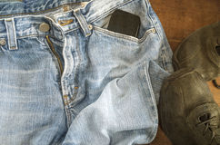 Detail of blue jeans with black shoes on wooden background Stock Photography