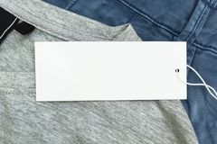 Detail of blue jeans and grey t-shirt with white blank tags, close up stock photo