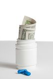 Detail of blue pills in front of container with inside rolled up dollars on white background Stock Photos