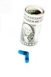 Detail of blue pills in front of rolled up dollars on white background Stock Images