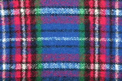Detail of blue-red-white-green checkered tartan wool blanket with fringe. Detail of blue-red-white-green checkered tartan wool blanket with fringe under white Royalty Free Stock Photography