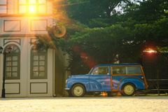 Detail of Blue retro car and green tree background with lighting flare effect. Royalty Free Stock Photo