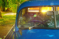Detail of Blue retro car and green tree background with lighting flare effect. Stock Photo