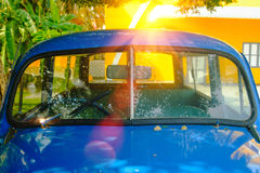 Detail of Blue retro car and green tree background with lighting flare effect. Royalty Free Stock Photos