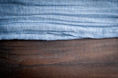 Detail of blue with tiny stripes material on dark wooden backgro Royalty Free Stock Photo