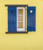 Detail of blue window with hearts and yellow wall. Complimentary colours royalty free stock images