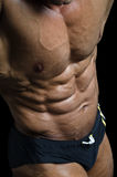Detail of bodybuilder torso: ripped abs and pecs. Detail of male bodybuilder torso: ripped abs and pecs, dark background Royalty Free Stock Photography