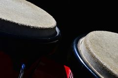 Detail of bongo drums macho on right and hembra on left, dark background. Sunbathing in morning sun stock images