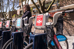 Detail of Boris bikes in line with woman in the background. Royalty Free Stock Image