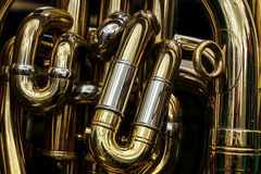 Detail of the brass pipes of a tuba. Abstract background showing the curves and joints of this polished brass band musical instrument Stock Photos
