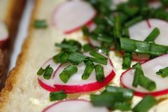 Detail of bread with butter, radishes and green onions. Slice of bread with radishes and onions Stock Photo