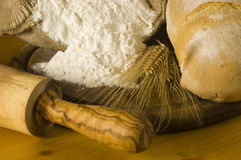 Detail of bread and flour. Detail of a rural kitchen with loaf of bread, wheat ears, white flour and rolling pin Stock Photos