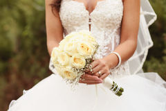 Detail of bride's roses bouquet and hands holding Royalty Free Stock Photos
