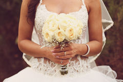 Detail of bride's roses bouquet and hands holding Royalty Free Stock Images