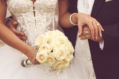 Detail of bride's roses bouquet and hands holding Stock Images