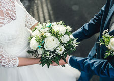Detail of bride`s white roses bouquet and hands holding Royalty Free Stock Photo