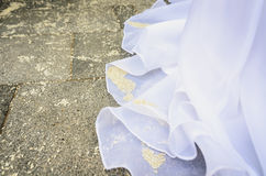 Detail of brides wedding dress with rice on the floor. Stock Photos