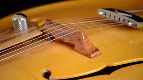 Detail of bridge, strings and efe of body of a classic electric jazz guitar rotating in black background. Classic Electric Guitar Jazz Rotating in Horizontal stock video