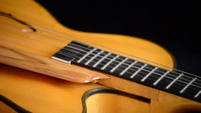 Detail of bridge, strings and efes of a jazz electric guitar gyrating at black background. Classic Electric Guitar Jazz Rotating in Horizontal stock footage