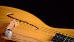 Detail of bridge, strings and efes of a jazz electric guitar gyrating at black background. Classic Electric Guitar Jazz Rotating in Horizontal stock video footage
