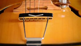 Detail of bridge, strings and efes of a jazz electric guitar gyrating at black background. Classic Electric Guitar Jazz Rotating in Horizontal stock video