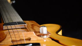 Detail of bridge, strings and efes of a jazz electric guitar rotating. Classic Electric Guitar Jazz Rotating in Horizontal stock video