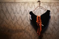 Brown bra and black underwear on hanger and dirty cement wall for background. Detail brown bra and black underwear on hanger and dirty cement wall for background Royalty Free Stock Photography