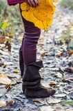 Brown leather boots and yellow leaf. Detail of the brown leather boots, legs and yellow leaf held by the girl Stock Photography
