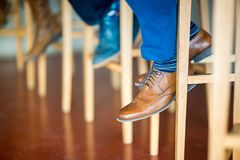 Detail of brown shoe of a gentleman sitting in the bar on a high stool Royalty Free Stock Photography