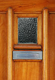Detail of brown wooden door with chrome mailslot Royalty Free Stock Images