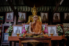 Detail of Buddha gold statues and statue of The famous monk named Luang Pu Mun in Old Buddhist temple. Stock Images