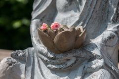 Detail of a Buddha statue with flowers in hands. Meditation pose Royalty Free Stock Image